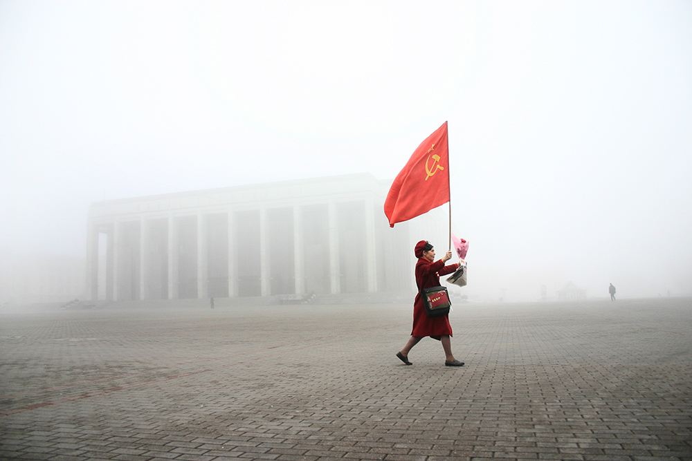 Woman carries USSR flag on Kastrychnickaja square  rally which marks the 1917 Bolshevik Revolution anniversary. This day is a state holiday in Belarus.